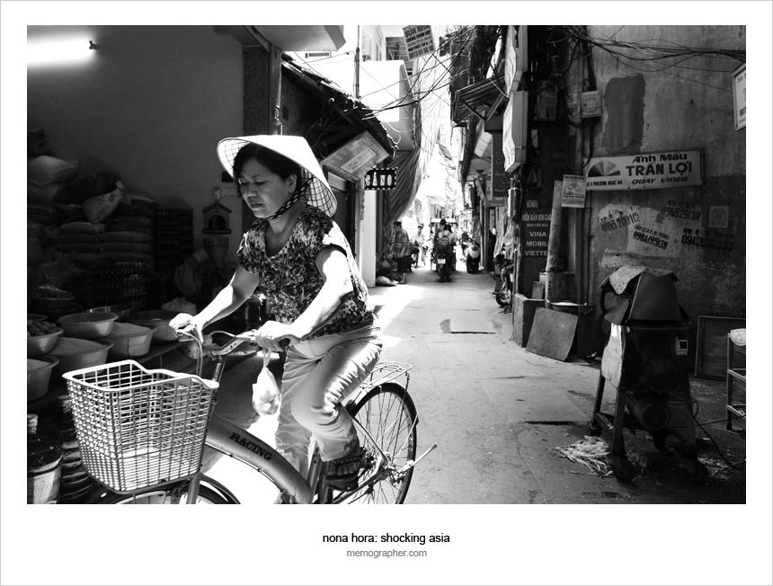 Vietnamese Woman on Bicycle. Hanoi, Vietnam