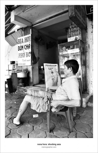 Vietnamese Man reading Newspaper. Hanoi, Vietnam