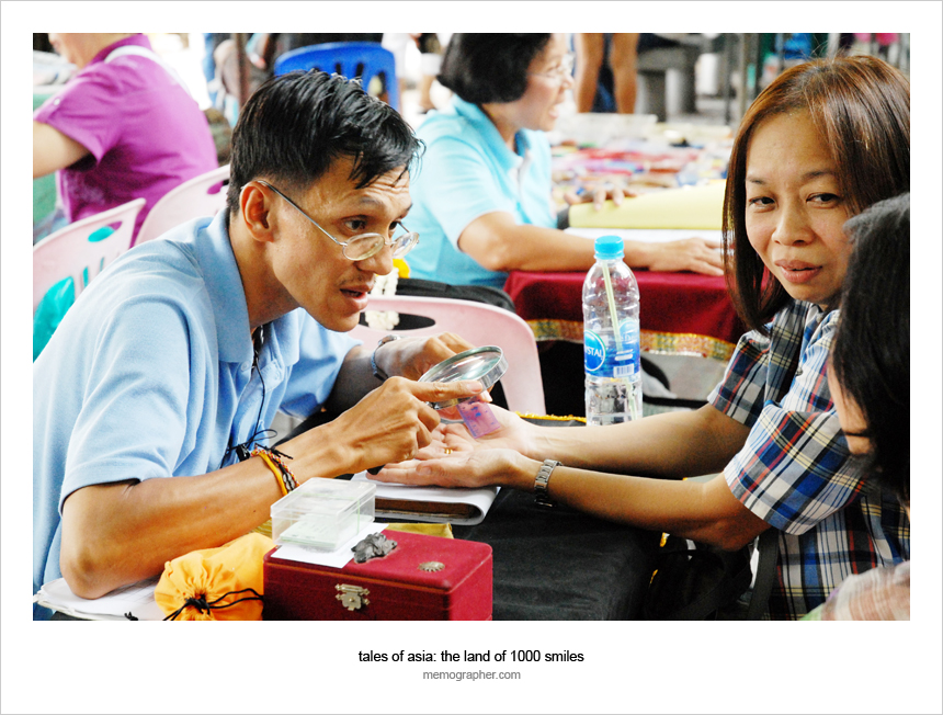 Thai palm reader foretelling the future of Thai Woman on the streets of Bangkok, Thailand