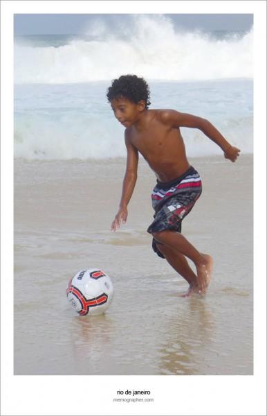 Boy playing football on Copacabana Beach. Rio de Janeiro, Brazil